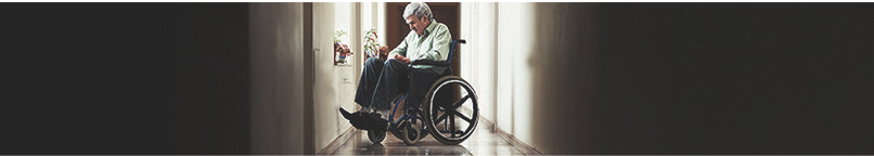 An elderly man who has experienced nursing home neglect sits in a wheelchair in an empty hallway