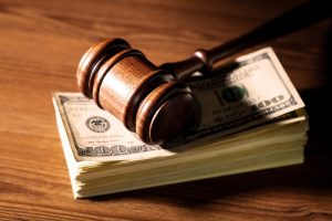 A gavel atop a stack of money from a Nexium lawsuit settlement