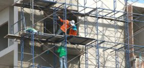 Laborers work on scaffolding at a building site, hoping that they won't need a Long Island construction accident lawyer